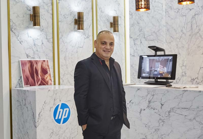 Ernest Azzam stands in front of a facade printed by HP printers.