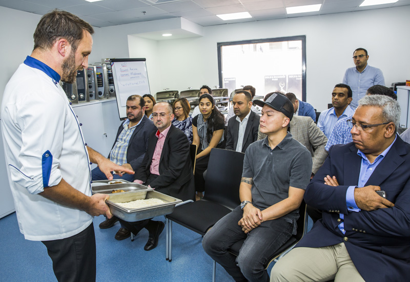 Sascha Barby shows his audience the quality of the food produced in a Rational combi-steamer.