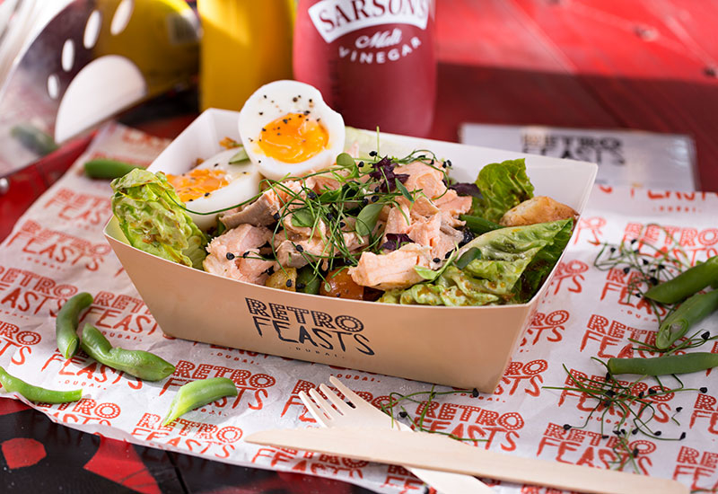 A salmon nicoise salad, served in a casual setting. The brand is meant to be vintage, fun, and playful, and is reflected in how food is served as well.
