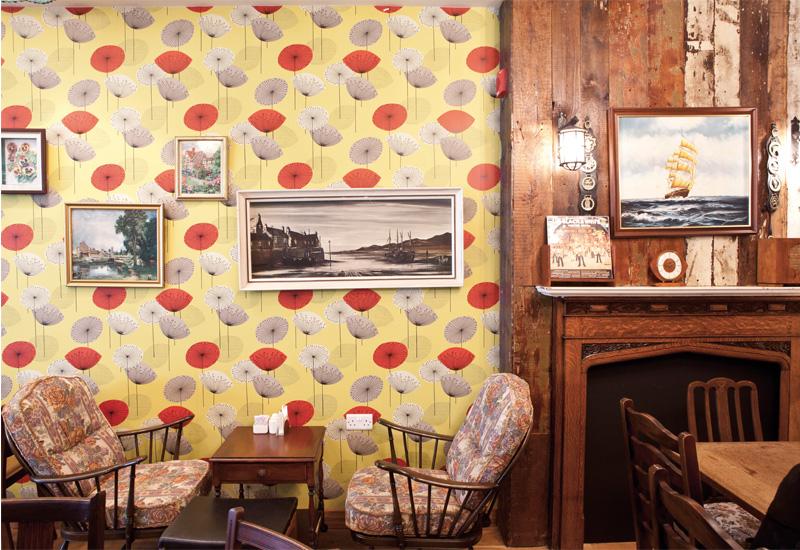 The popular Poppy wallpaper by Sanderson and a fireplace obtained from Cefn Coed Hospital in Swansea.