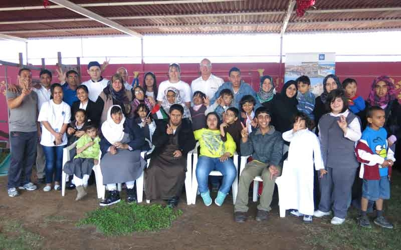 Employees from the Cove Rotana Resort with children from the Specialized Centre for Special Needs.