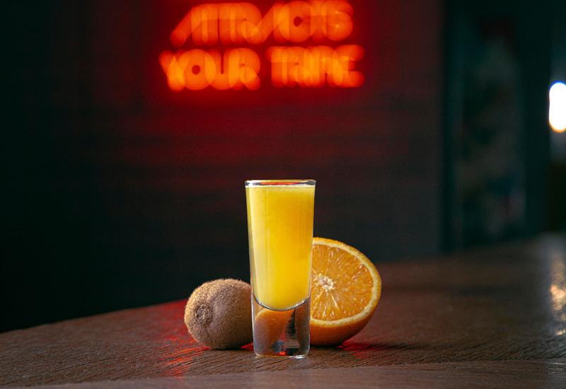 The shot comprises kiwi and orange juice